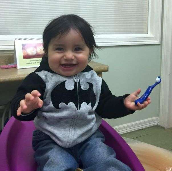 Little boy in Batman Jacket holding a toothbrush - Blume Pediatric Dentistry San Antonio, TX
