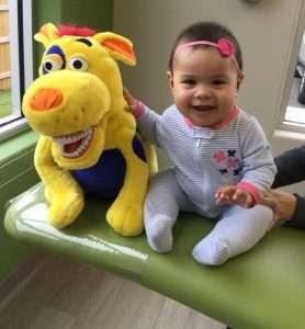 Baby girl sitting with a stuffed animal - Blume Pediatric Dentistry San Antonio, TX