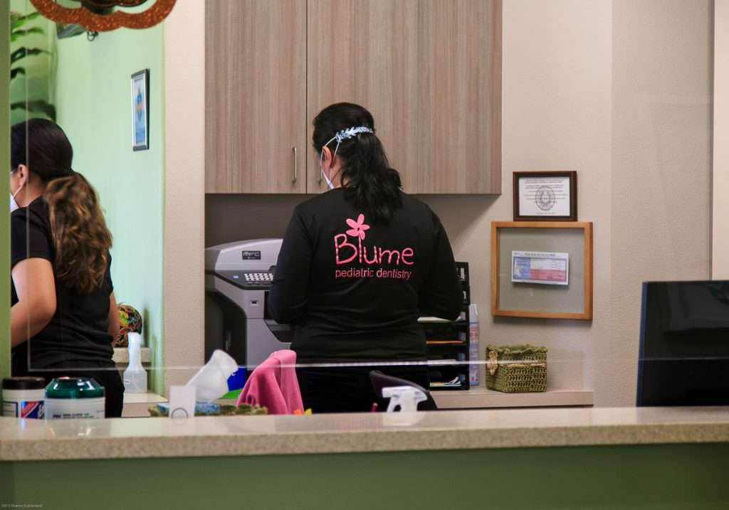 Female working wearing a Blume shirt - Blume Pediatric Dentistry San Antonio, TX