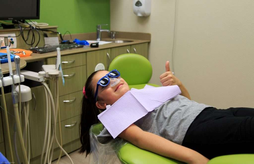 Young female patient giving a thumbs up - Blume Pediatric Dentistry San Antonio, TX