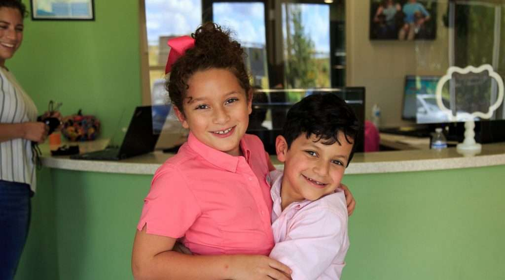 Young brother hugging his big sister - Blume Pediatric Dentistry San Antonio, TX